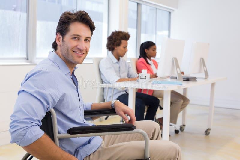 Hombre de negocios en silla de ruedas con incapacidad en el trabajo imagenes de archivo