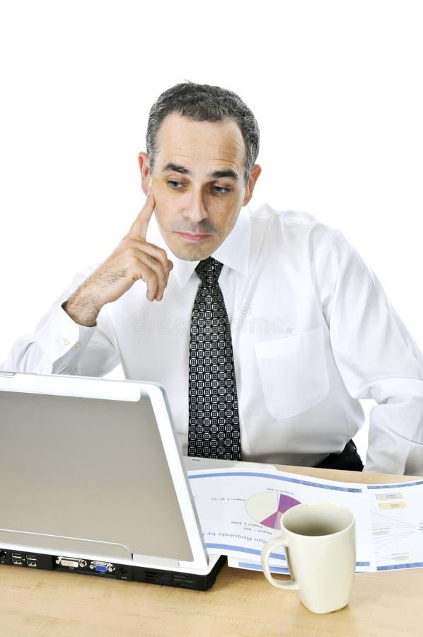 Hombre de negocios en su escritorio en el fondo blanco imagenes de archivo