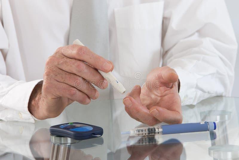 Hombre de negocios en su oficina con sangre de medición de la diabetes del inicio fotografía de archivo