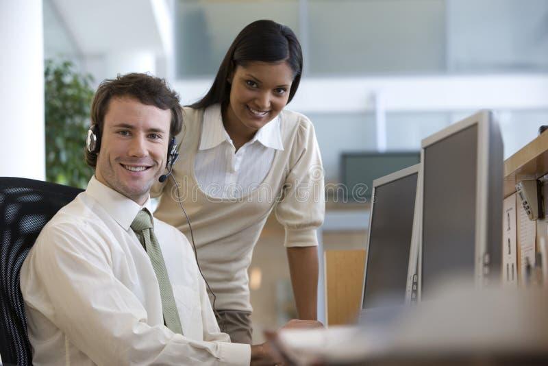 Hombre de negocios en su ordenador con el colega fotografía de archivo