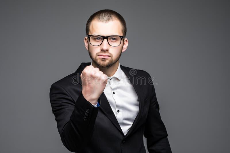 Hombre de negocios en sus años 40, enojado y sacudiendo su puño de una manera que amenaza aislado en gris imagen de archivo libre de regalías