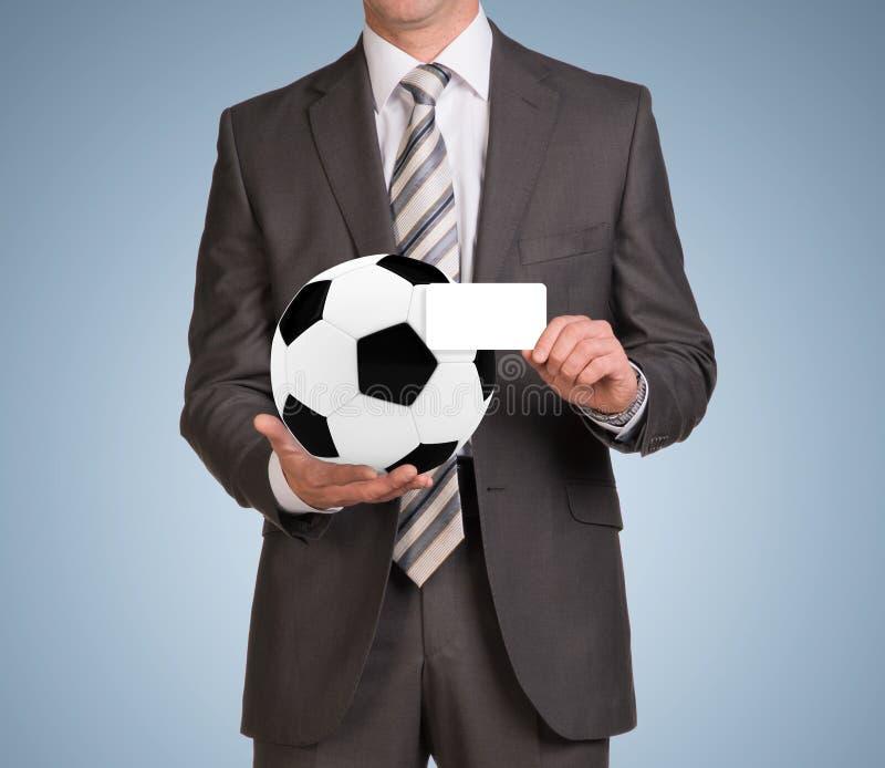 Hombre de negocios en tarjeta vacía y fútbol del control del traje imagen de archivo