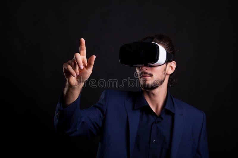 Hombre de negocios en traje con auriculares de VR en la cabeza que toca un virtual fotos de archivo