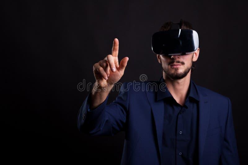 Hombre de negocios en traje con auriculares de VR en la cabeza que toca un virtual foto de archivo