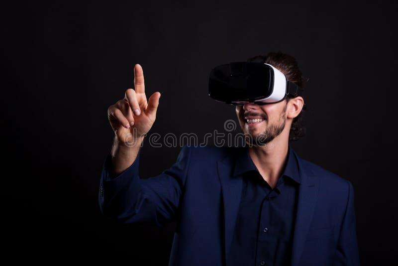 Hombre de negocios en traje con auriculares de VR en la cabeza que toca un virtual fotografía de archivo