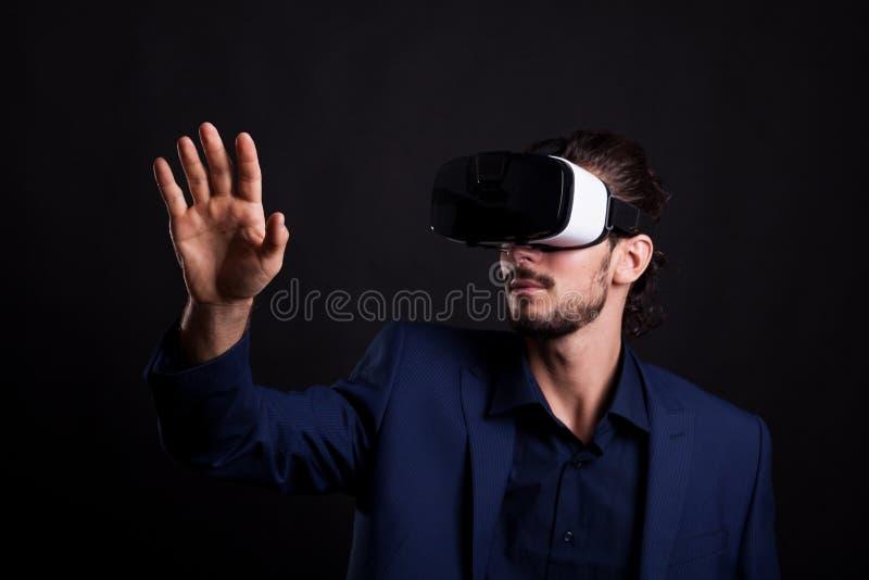 Hombre de negocios en traje con auriculares de VR en la cabeza que toca un virtual imágenes de archivo libres de regalías