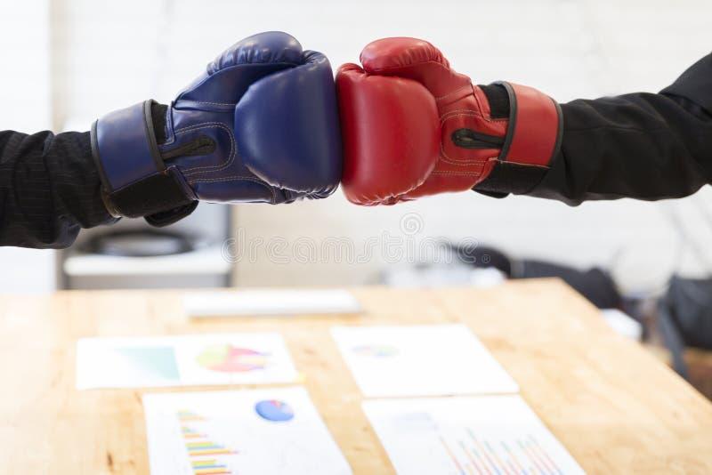 Hombre de negocios en traje con los guantes de boxeo rojos y azules foto de archivo libre de regalías