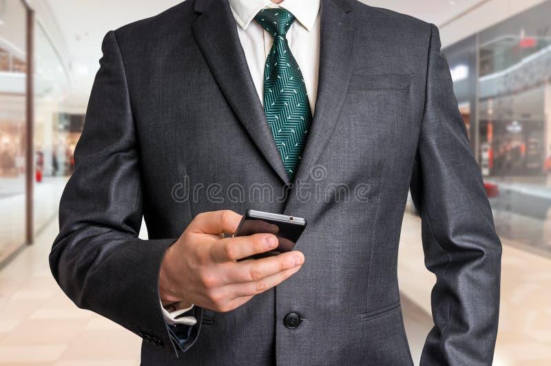 Hombre de negocios en traje negro con el teléfono móvil imagen de archivo libre de regalías