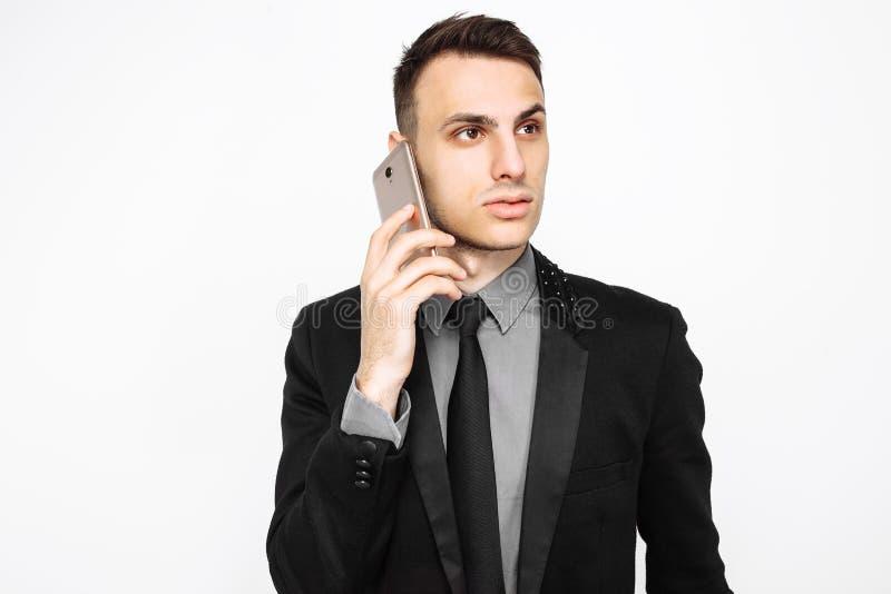 Hombre de negocios en traje negro que habla en el teléfono aislado en los vagos blancos imágenes de archivo libres de regalías