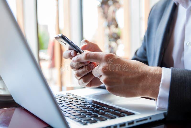 Hombre de negocios en traje negro usando el teléfono elegante móvil y trabajo en el ordenador portátil, de la ojeada y escritura  foto de archivo libre de regalías