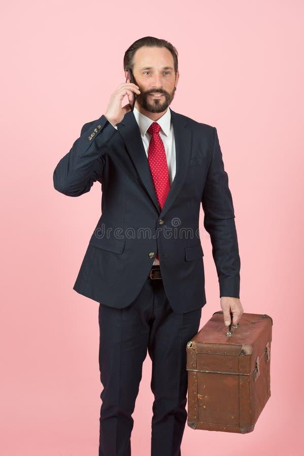 Hombre de negocios en traje negro y lazo rojo con la cartera del vintage que hablan sobre el teléfono en fondo rosado de la pared foto de archivo