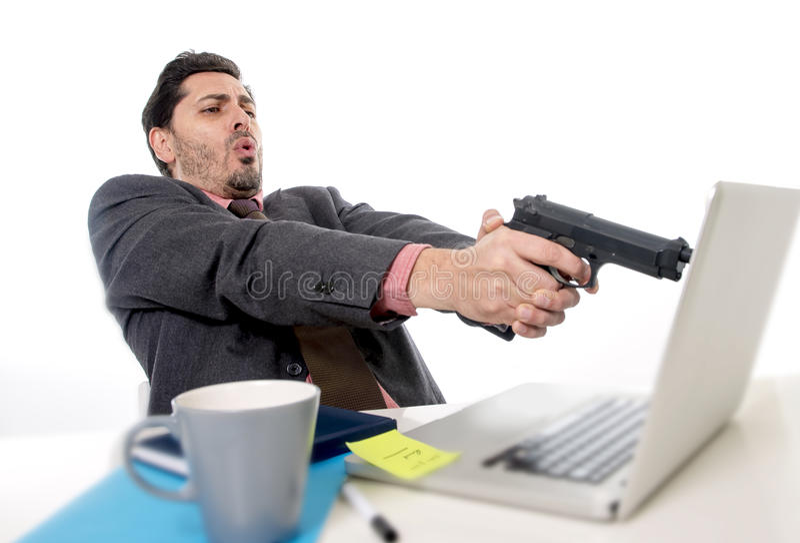 Hombre de negocios en traje y lazo que se sienta en el escritorio de oficina que trabaja en el ordenador que señalan el arma al o fotografía de archivo libre de regalías