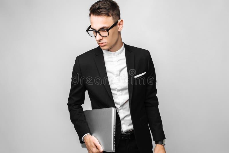 Hombre de negocios en traje y vidrios con el ordenador portátil aislado en vagos grises fotos de archivo libres de regalías