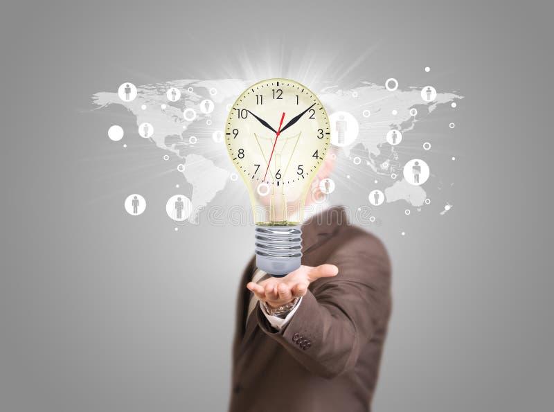 Hombre de negocios en un bulbo del control del traje con el reloj imagenes de archivo