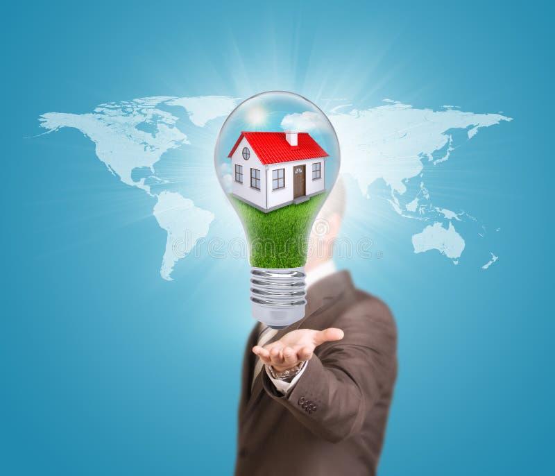 Hombre de negocios en un bulbo del control del traje con la casa imagen de archivo libre de regalías