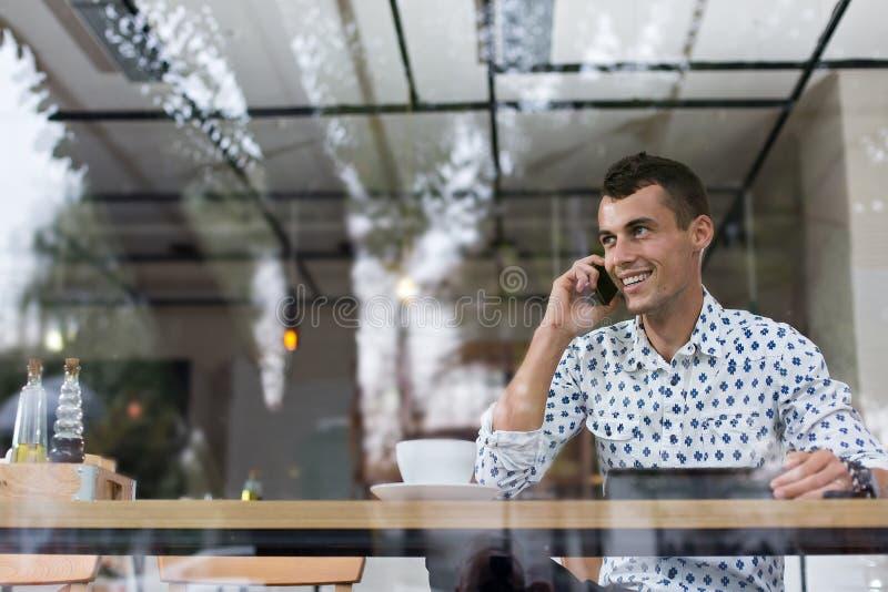 Hombre de negocios en un café que habla en el teléfono fotografía de archivo libre de regalías