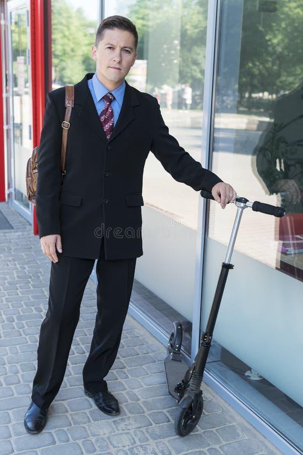 Hombre de negocios en un edificio de oficinas con la vespa fotos de archivo libres de regalías