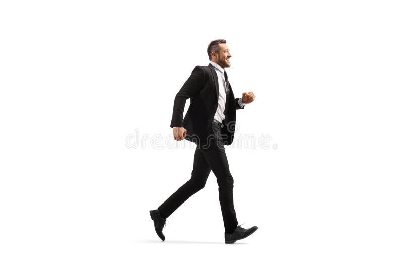 Hombre de negocios en un traje negro que corre y que sonríe fotografía de archivo