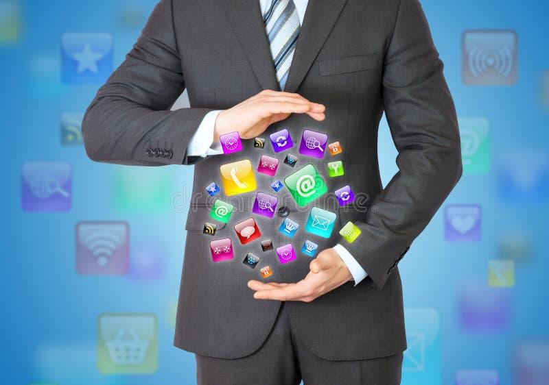 Hombre de negocios en un traje que lleva a cabo iconos de un app fotos de archivo