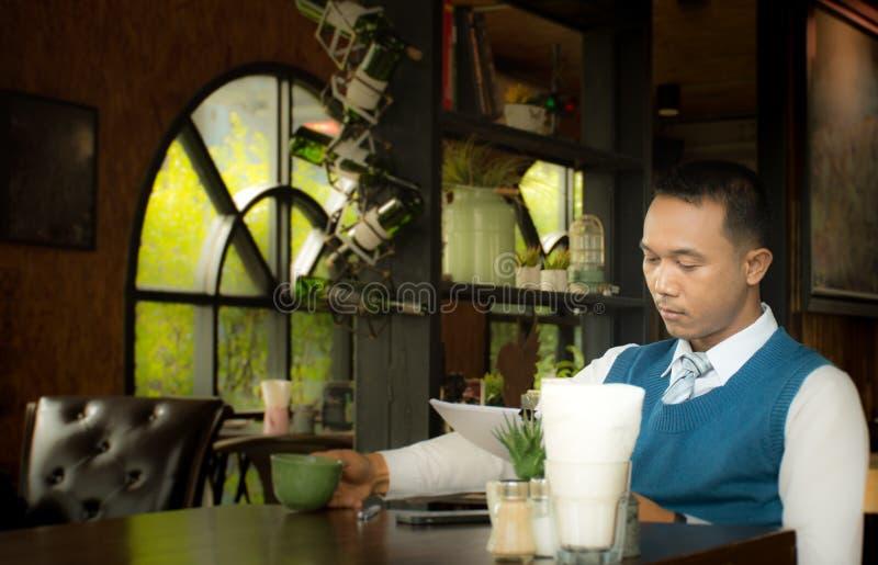 Hombre de negocios en una cafetería que lee un documento del contrato fotos de archivo libres de regalías