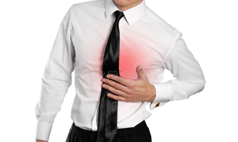 Hombre de negocios en una camisa y un lazo blancos que llevan a cabo su dolor de pecho adentro fotografía de archivo libre de regalías