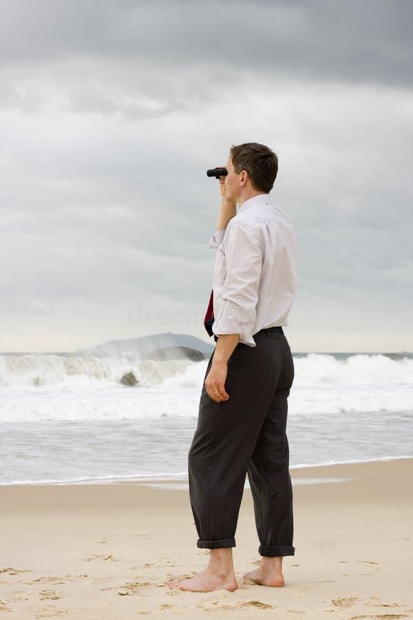 Hombre de negocios en una playa que busca con los prismáticos imagenes de archivo