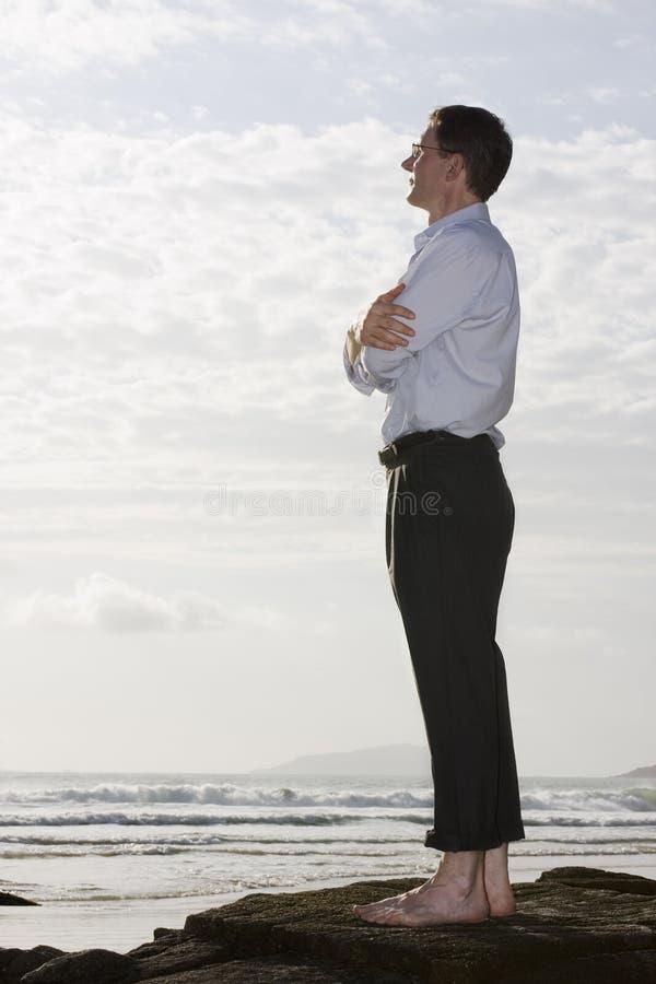 Hombre de negocios en una roca por el mar imágenes de archivo libres de regalías
