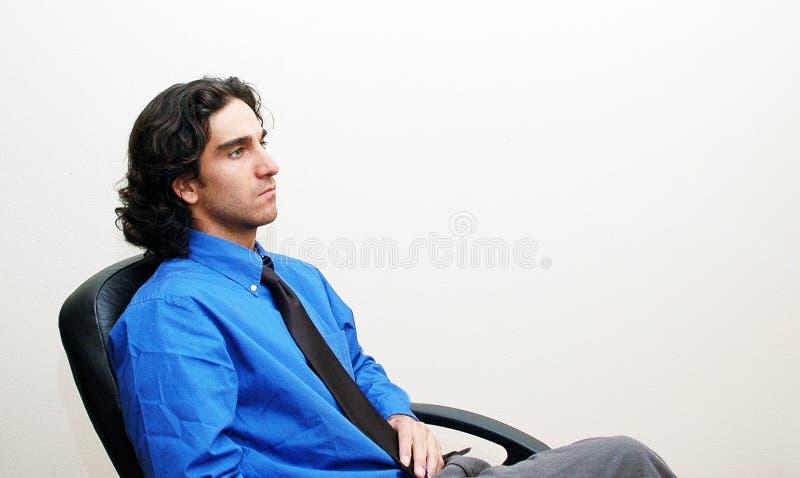Hombre de negocios en una silla foto de archivo