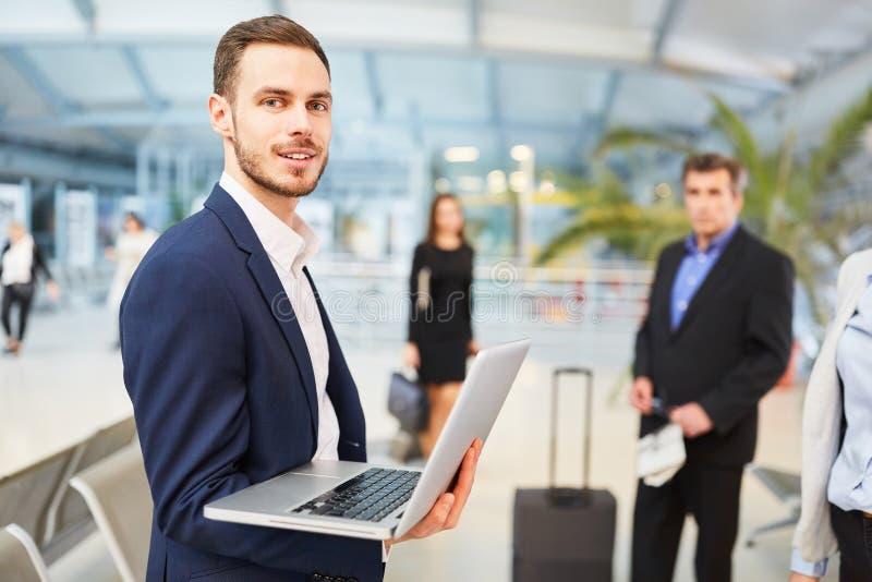 Hombre de negocios en viaje de negocios usando el ordenador portátil foto de archivo libre de regalías