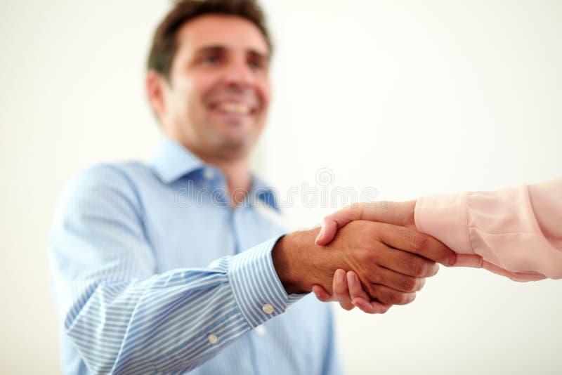 Hombre de negocios encantador adulto que da las manos que saludan imagenes de archivo