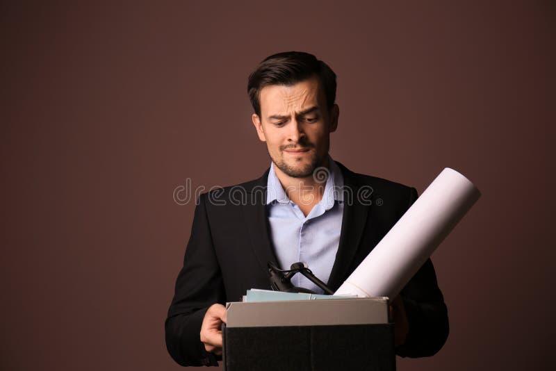 Hombre de negocios encendido emocional con la materia personal en fondo del color foto de archivo
