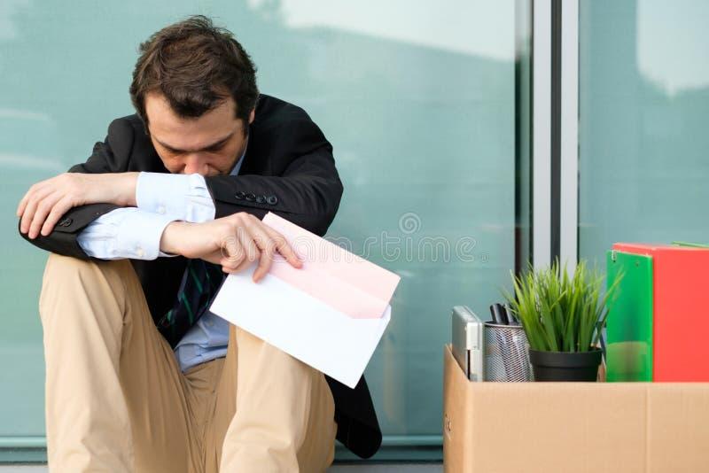 Hombre de negocios encendido que lee el aviso de la terminación del trabajo imágenes de archivo libres de regalías
