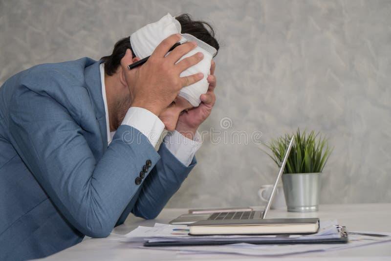 Hombre de negocios enfermo que toca su cabeza con las manos mientras que usa lapto imagen de archivo libre de regalías