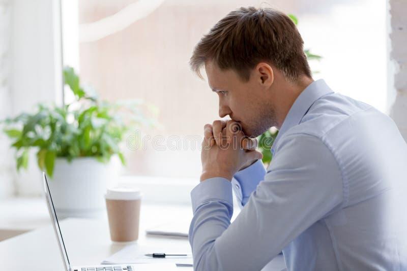 Hombre de negocios enfocado que se sienta en la oficina que trabaja y que piensa imágenes de archivo libres de regalías