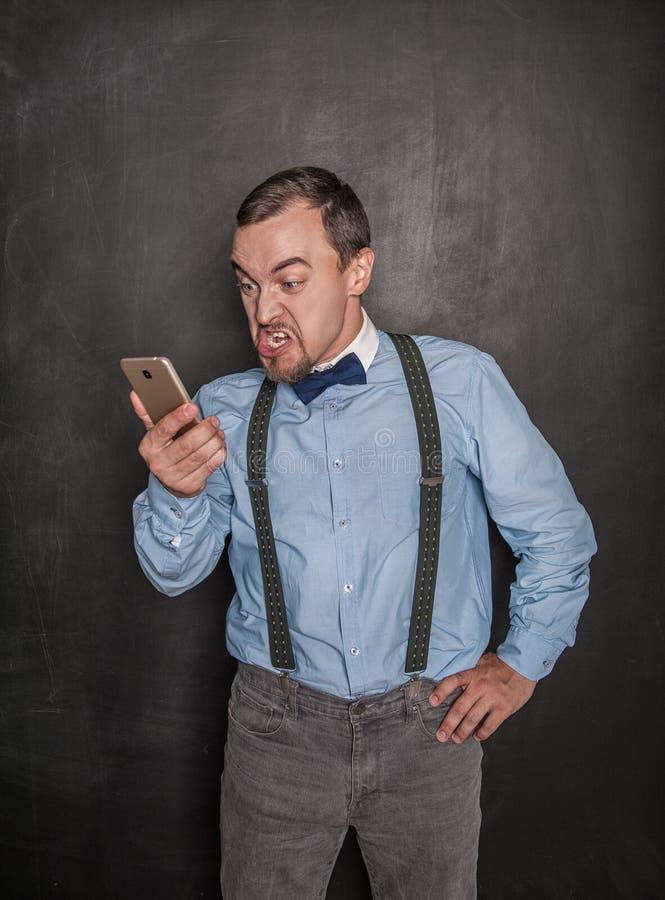Hombre de negocios enojado con el teléfono móvil en la pizarra fotografía de archivo libre de regalías