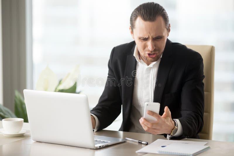 Hombre de negocios enojado debido a llamada de teléfono inoportuna foto de archivo libre de regalías