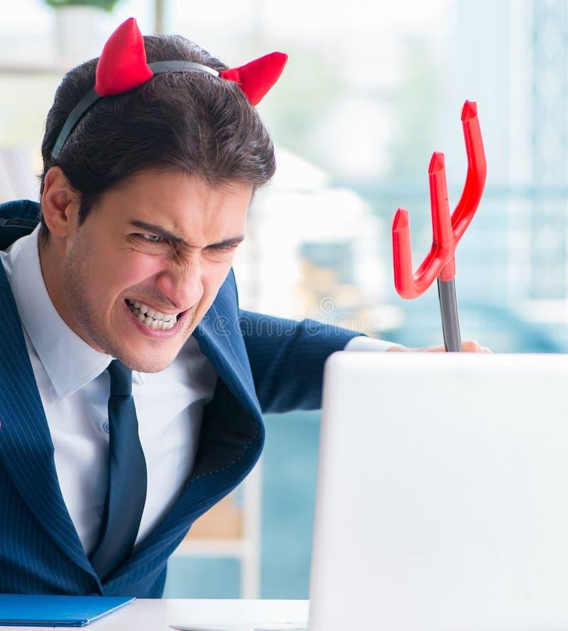 Hombre de negocios enojado del diablo en la oficina imagenes de archivo