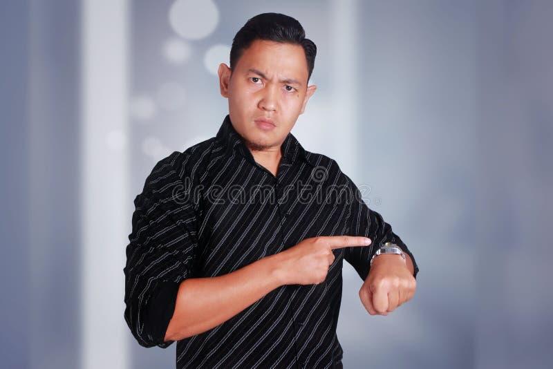 Hombre de negocios enojado del encargado mientras que señala su reloj que muestra tiempo foto de archivo libre de regalías