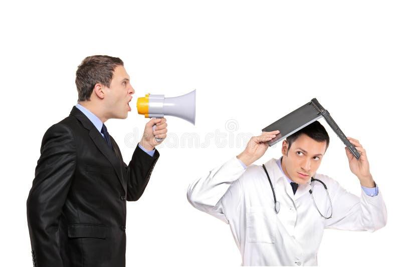 Hombre de negocios enojado que grita a un doctor imágenes de archivo libres de regalías