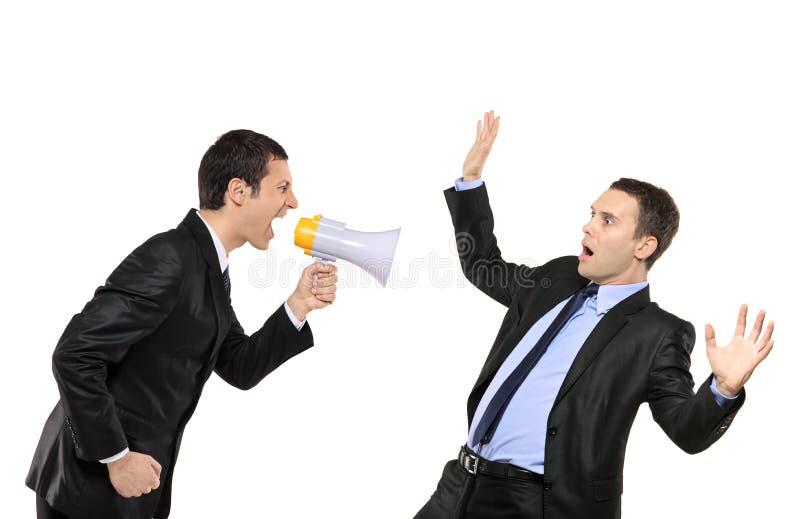 Hombre de negocios enojado que grita vía el megáfono a un hombre imagenes de archivo