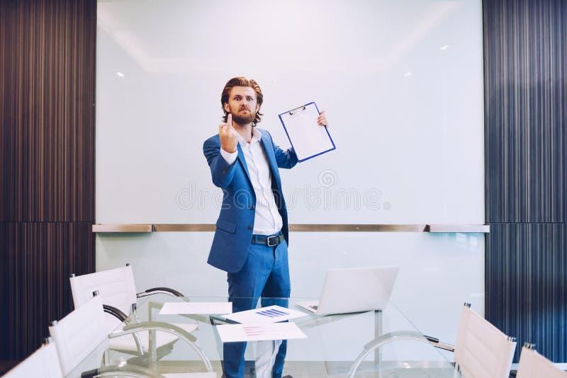 Hombre de negocios enojado que muestra el dedo medio en sala de reunión imagen de archivo libre de regalías