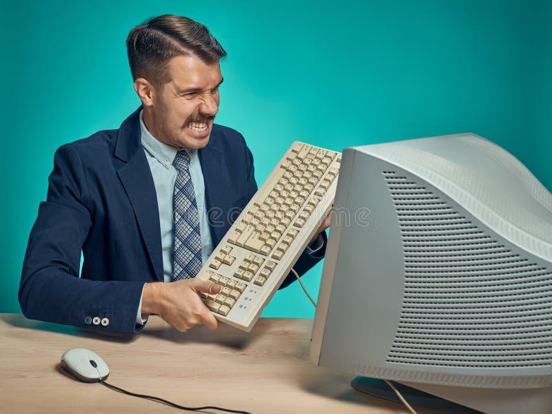 Hombre de negocios enojado que rompe el teclado contra fondo azul fotografía de archivo libre de regalías