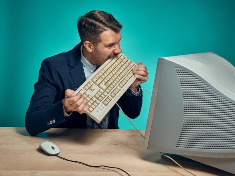 Hombre de negocios enojado que rompe el teclado contra fondo azul imagen de archivo libre de regalías