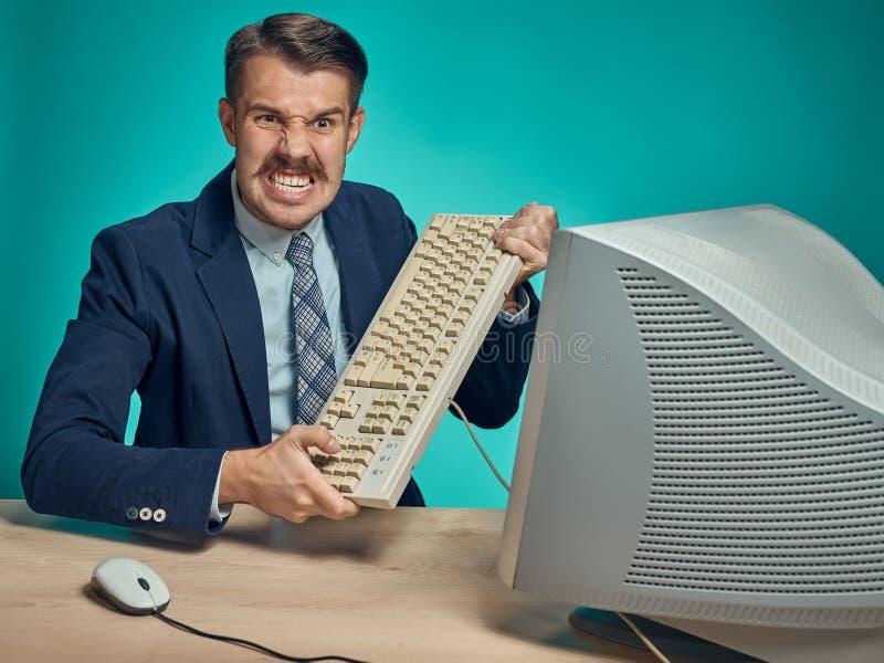 Hombre de negocios enojado que rompe el teclado contra fondo azul foto de archivo libre de regalías