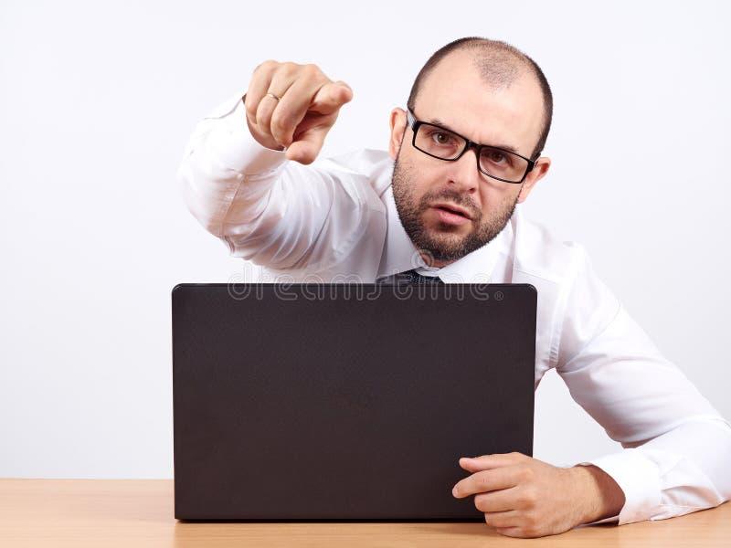 Hombre de negocios enojado que se sienta en su escritorio fotos de archivo libres de regalías