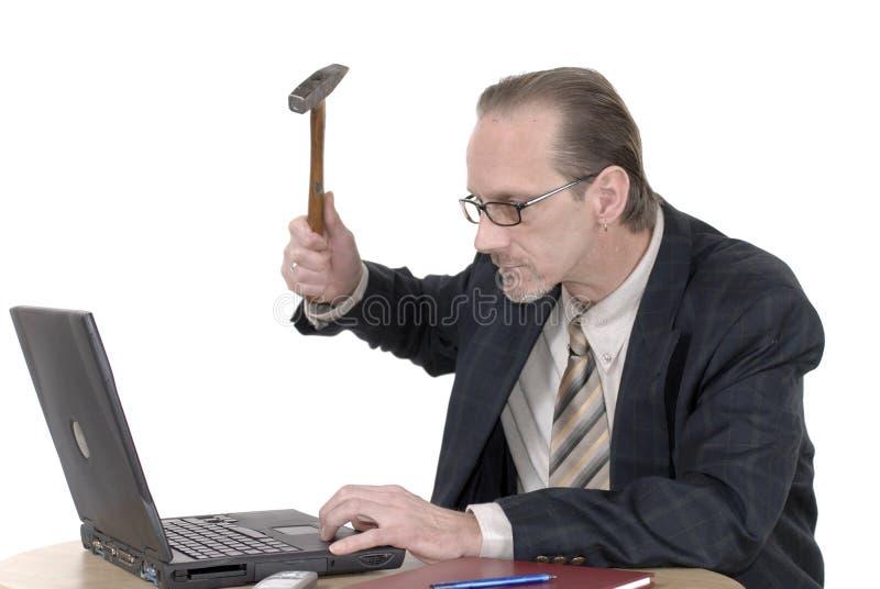 Hombre de negocios enojado que trabaja en la computadora portátil imagen de archivo