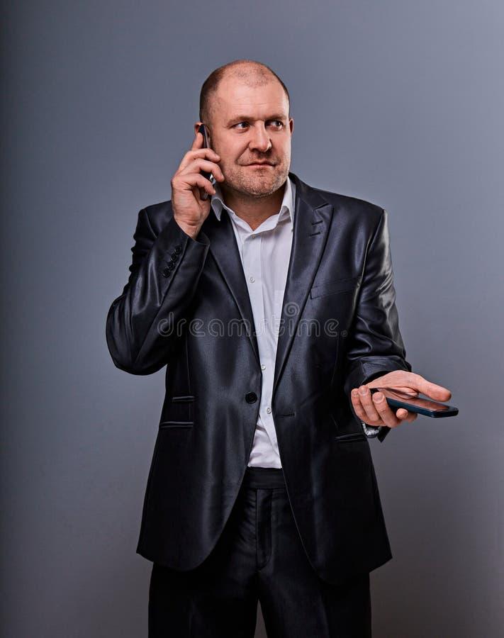 Hombre de negocios enojado subrayado de pensamiento de la duda que habla en el teléfono móvil muy emocional en traje de la oficin foto de archivo