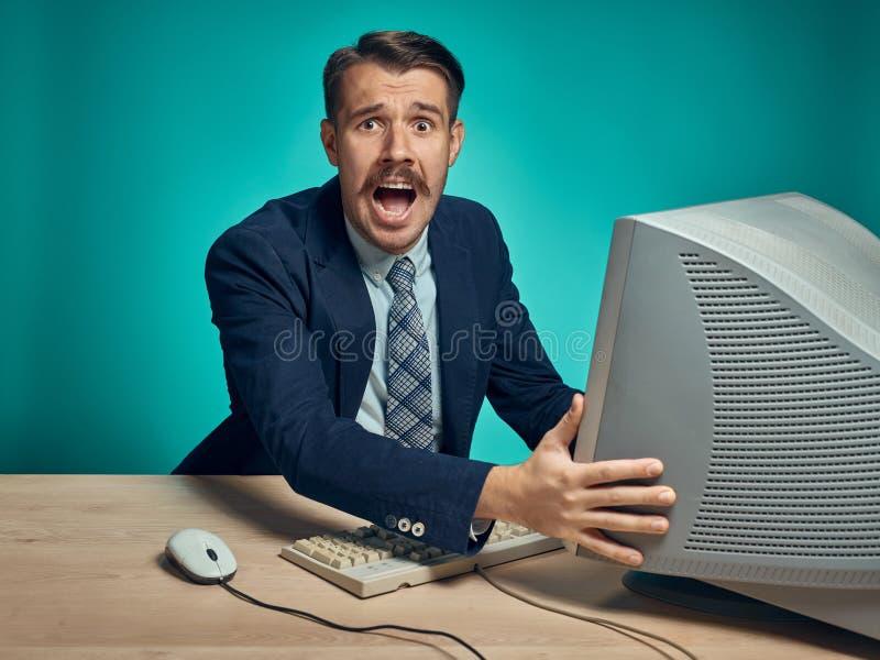 Hombre de negocios enojado usando un monitor contra fondo azul imagenes de archivo