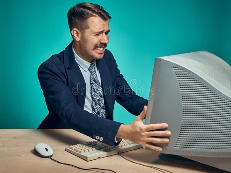 Hombre de negocios enojado usando un monitor contra fondo azul imágenes de archivo libres de regalías