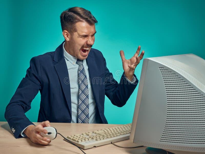 Hombre de negocios enojado usando un monitor contra fondo azul fotos de archivo